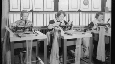 Three women working at machines.