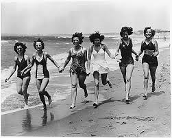 Women running on the beach in the 1940s.